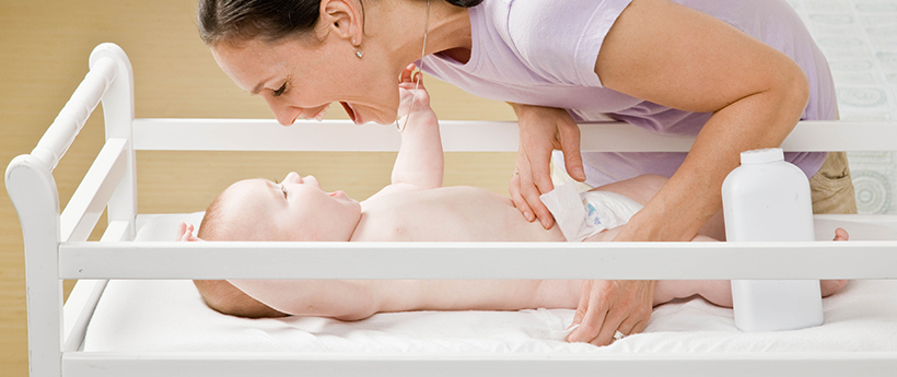 Devoted mother playing with baby on changing table