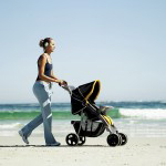side view of a woman pushing a stroller on the beach