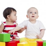 two babies girls playing together with color block toys